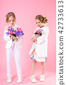 Twins girls in light clothes with bouquets of flowers stand on a pink background. 42733613