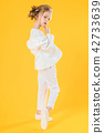 A teenage girl in white clothes posing on a yellow background. The girl lowered her jacket to her 42733639