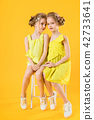 Twins girls are sitting on a chair on a yellow background. 42733641