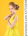 Girl posing on yellow background. 42733648