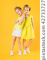 The girls of the twins stand together on a yellow background. 42733727