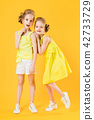 The girls of the twins stand together on a yellow background. 42733729