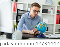 A young man sits in the office at a computer desk and in front of him stands a globe. 42734442