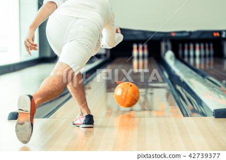 Young man playing bowling. 42739377