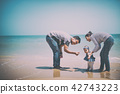 Asia parents playing with daughter at the sea. 42743223