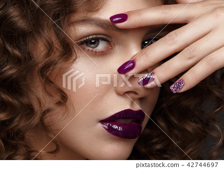 Beautiful girl with evening make-up, purple lips, curls and design manicure nails. beauty face. 42744697