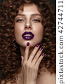 Beautiful girl with evening make-up, purple lips, curls and design manicure nails. beauty face. 42744711