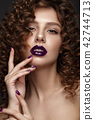 Beautiful girl with evening make-up, purple lips, curls and design manicure nails. beauty face. 42744713