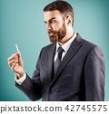 Bewildered businessman looking on cigarette in hand. 42745575