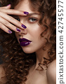 Beautiful girl with evening make-up, purple lips, curls and design manicure nails. beauty face. 42745577