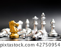 Gold horse in chess game face with another silver 42750954