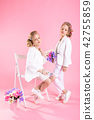 Twins girls in light clothes with bouquets of flowers posing near a chair on a pink background. 42755859