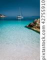Beautiful azure blue lagoon with sailing catamaran yacht boat at anchor. Pure white pebble beach 42755910