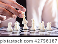 Hand of confident businessman use king chess piece white playing 42756167