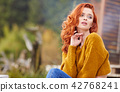 Autumn woman relaxing on a wooden terrace in the morning. Female 42768241