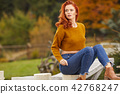 Autumn woman relaxing on a wooden terrace in the morning. Female 42768247