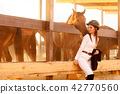rider woman in helmet with whip near horses 42770560