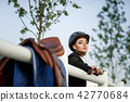 elegant rider woman in helmet with whip 42770684