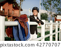elegant rider woman in helmet with whip 42770707