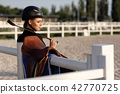 elegant rider woman in helmet with whip 42770725