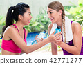 Women friends relaxing after fitness exercise 42771277
