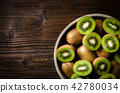 Kiwi fruits in bowl over wooden background 42780034