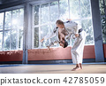 Two judo fighters showing technical skill while practicing martial arts in a fight club 42785059