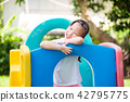 Little girl smiling while playing in playground 42795775