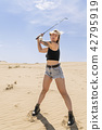 Portrait of a woman with golf putter 42795919