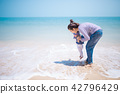A asia mather playing with her daughter at the sea. 42796429