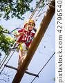 Little brave caucasian girl at outdoor treetop climbing adventure park 42796540