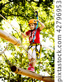 Little brave caucasian girl at outdoor treetop climbing adventure park 42796953