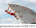 Photo of young sportsman in red shorts hanging on wall for rock climbing against blue sky with 42801455