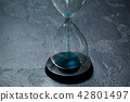 Photo of glass hourglass with blue sand on black stone background 42801497