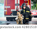 Photo of young fireman squatting next to service dog near fire engine 42801510