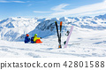 snowboarder and skiier sitting on snow and see at mountains 42801588