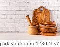 Wooden tableware on a white table. 42802157