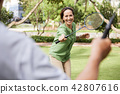 Woman enjoying game of badminton 42807616