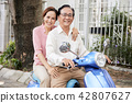 Senior couple riding on scooter 42807627