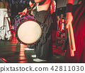 Japanese musicians play on Taiko drums o-kedo okedo-daiko on a stage. Musical instrument of Asia 42811030