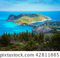 View to Assos village and beautiful blue sea. Cypress trees in foreground. Kefalonia island, Greece 42811665