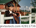 elegant rider woman in helmet with whip 42811736