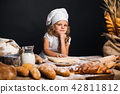 Little girl kneading dough at table 42811812