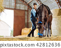 Professional female rider feeling good while visiting horse in stable 42812636
