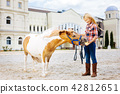 Blonde-haired smiling cowboy girl feeding her little pony 42812651