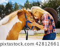 Caring cowboy girl feeling emotional while seeing her cute pony 42812661