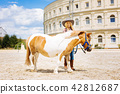 Beaming beautiful cowboy girl taking care of her pony 42812687
