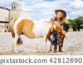 Amused cowboy girl having fun with pony outside stable 42812690