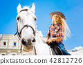 Girl with long blonde hair feeling nice while riding horse 42812726