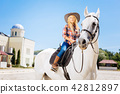 Blonde-haired cowboy girl wearing stylish clothes riding horse 42812897